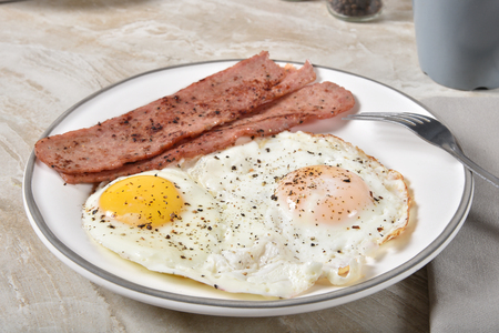 Photo for Delicious fried egg breakfast with crispy strips of turkey bacon - Royalty Free Image