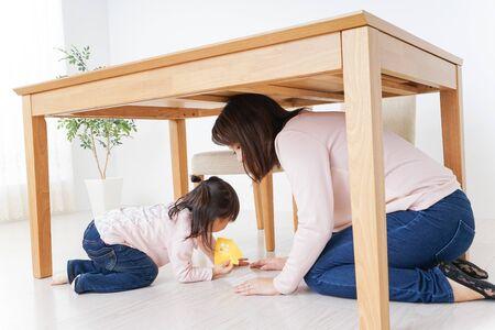 Foto de A parent and child huddling under a table - Imagen libre de derechos