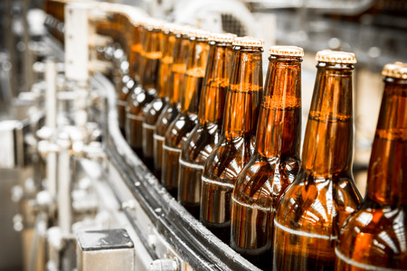 Foto de Beer bottles on the conveyor belt, brewery - Imagen libre de derechos