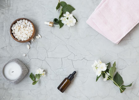 Photo pour Spa setting flatlay with bath salt, jasmine oil bottle and flowers, towel and natural soap. Spa and wellness still life - image libre de droit