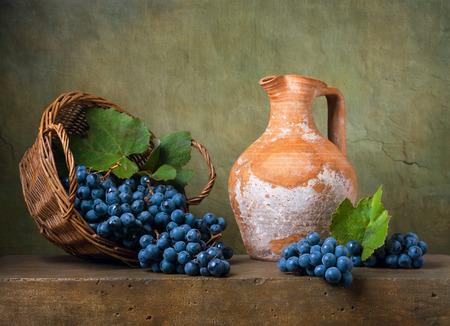 Foto de Still life with grapes on a basket and jug - Imagen libre de derechos