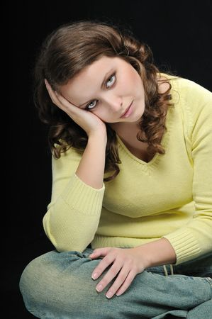 Young beautiful woman (teenager) in depression isolated on black background