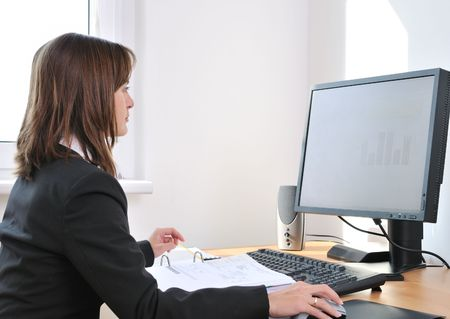 Business person (young woman) works at table with computer - office interior