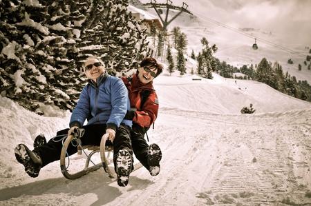 Photo pour Active senior couple on sledge having fun in mountain snowy country - image libre de droit
