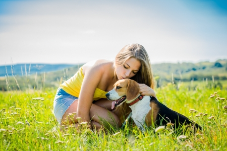 Young woman kissing her dog - outdoor in nature
