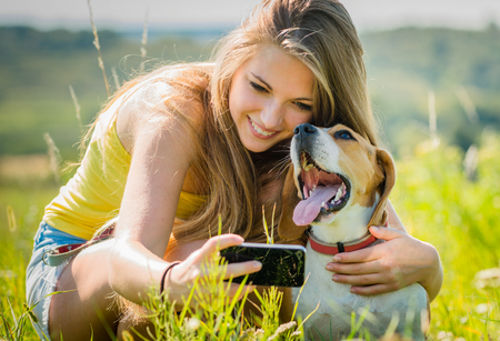 Photo pour Teen girl taking photo of herself and her dog with mobile phone camera - image libre de droit
