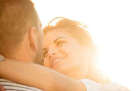 Photo pour Happy couple having great time together - photographed at sunset against sun - image libre de droit