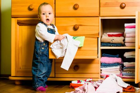 Foto de Domestic chores - baby throws out clothes - Imagen libre de derechos