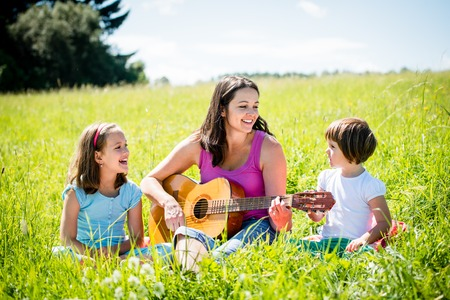 Photo for Mother playing guitar in nature to children - Royalty Free Image