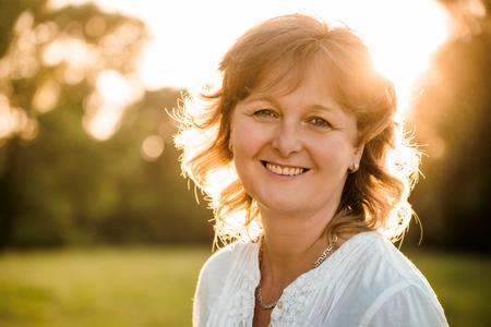 Photo pour Outdoor portrait of mature woman - in nature at sunset - image libre de droit