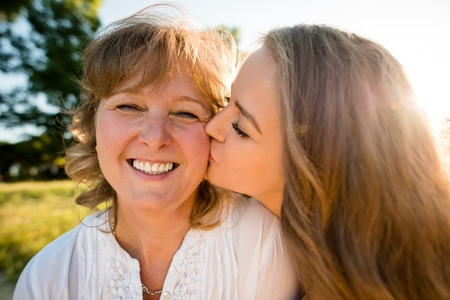 Teenage daughter kissing her mother outdoor in nature with sun in background, wide angle