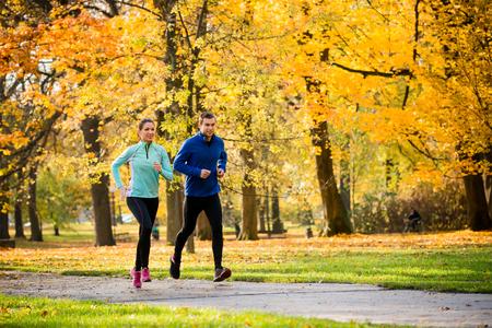 Photo pour Young couple jogging together in park - autumn season - image libre de droit