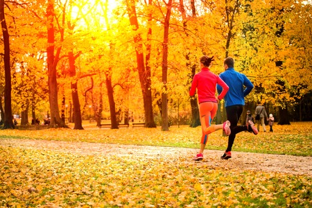 Photo pour Young couple running together in park - fall nature - image libre de droit