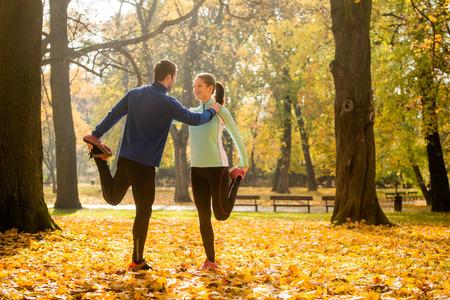 Photo pour Young couple stretching legs before jogging in autumn nature - image libre de droit