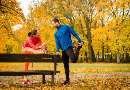 Photo for Young couple stretching muscles on bench before jogging in autumn nature - Royalty Free Image