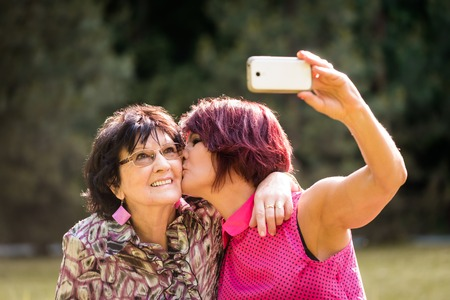 Senior woman is taking selfie with mobile phone while kissing her elderly mother