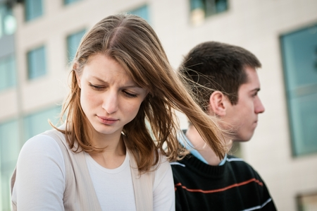 Foto de Portrait of young woman and man outdoor on street having relationship problems - Imagen libre de derechos