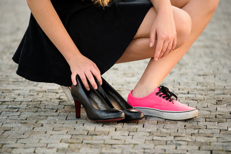 Foto de Young woman  on street in sneakers and high heels shoes are next to her - Imagen libre de derechos