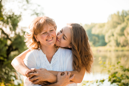 Photo pour Mature mother hugging with her teen daughter outdoor in nature on sunny day - image libre de droit