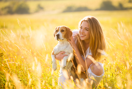Photo pour Teen girl having fun with beagle dog outdoor in nature on sunny summer day - image libre de droit