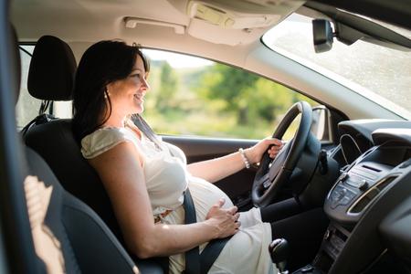 Photo pour Pregnant woman driving her car, wearing seat belt. - image libre de droit