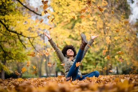Foto de Autumn woman sitting with arms raised - Imagen libre de derechos