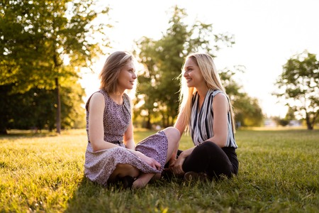 Photo for Best friends forever sitting together on grass - Royalty Free Image