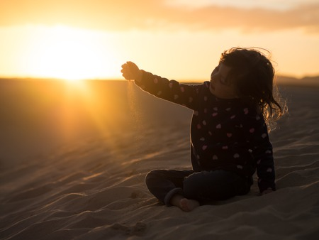 Photo for Little girl playing with sand during sunset - Royalty Free Image