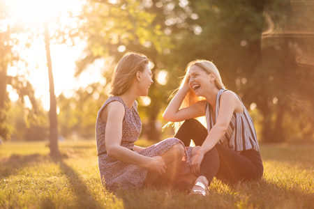 Photo for Candid shot of young women sitting in park - Royalty Free Image