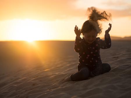 Photo for Girl child having fun in desert during sundown - Royalty Free Image