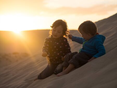 Photo for Kids sitting on dune playing with sand particles - Royalty Free Image