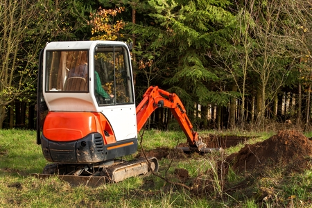 Photo for Work on the construction site of an ecological house. The excavator adjusts the terrain. A small digger in the garden - Royalty Free Image