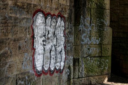 Foto de The red and white words of the graffiti on the bridge - Imagen libre de derechos