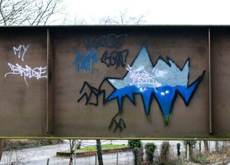 Foto de some distinctive blue and white graffiti on a brown bridge - Imagen libre de derechos