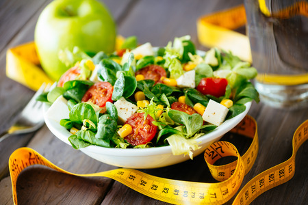 Foto de Fitness salad and measuring tape on rustic wooden table  Mixed greens, tomatos, diet cheese, olive oil and spices for healthy lifestyle concept  - Imagen libre de derechos