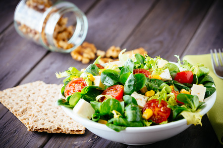 Photo for Dieting healthy salad and crackers on rustic wooden table  Mixed greens, tomatos, diet cheese, olive oil and spices for healthy lifestyle concept  - Royalty Free Image