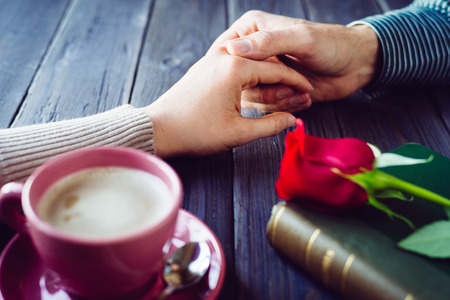 Photo pour Romantic lovers dating  Male and female hands caressing with love  Couple on secret dating at coffee shop  - image libre de droit