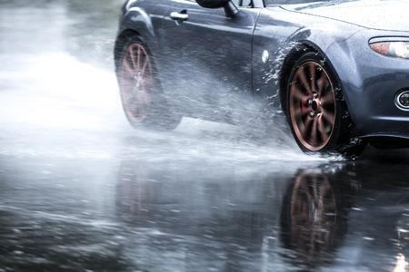 Photo pour Sports car driven on rainy roads close up on a wheel with motion blur effect - image libre de droit