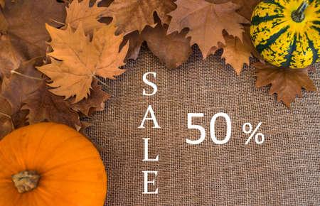 Foto de 50% sale text, on sack surface with autumn dry leaves and pumpkins - Imagen libre de derechos