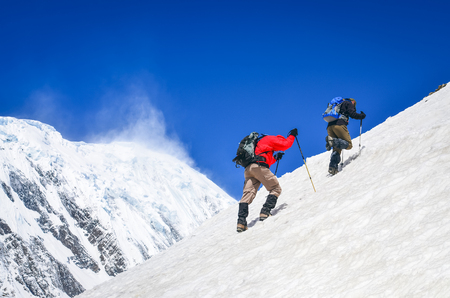 Photo pour Two mountain backpackers walking on steep hill with snowed peaks background, Himalayas - image libre de droit