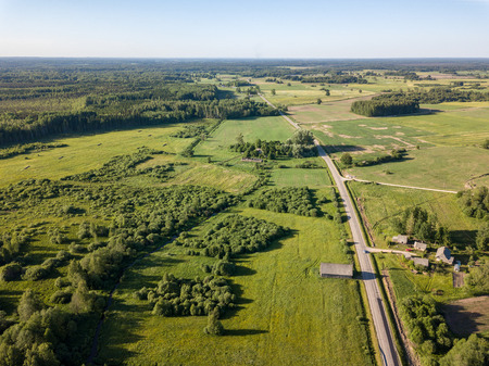 Photo for drone image. asphalt road surrounded by pine forest and fields from above in latvia - Royalty Free Image