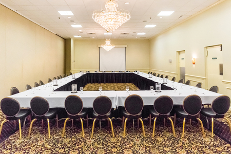 Foto de Hotel conference meeting room with tables and chairs set up facing each other. Projection screen is in back of room. - Imagen libre de derechos