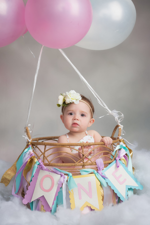 One year old caucasian girl in cute hot air balloon basket for first birthday