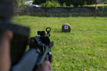 Photo for A girl shoots a target from a pneumatic gun. A view from behind the shoulder. - Royalty Free Image