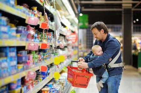 Photo pour Father and his son at supermarket together - image libre de droit