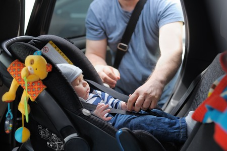 Photo pour Father fasten his little son in car seat - image libre de droit
