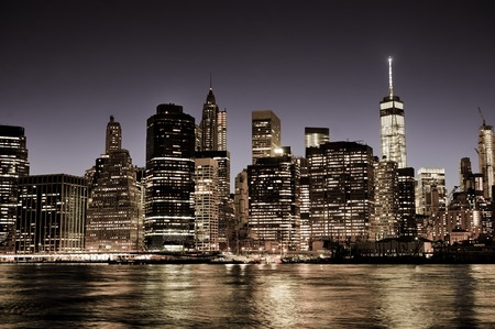 Foto de New York City Manhattan downtown skyline at night with illuminated skyscrapers, vintage filter - Imagen libre de derechos