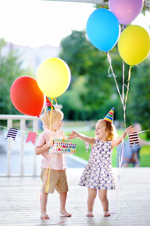 Photo pour Little boy and girl having fun and celebrate birthday party with colorful balloons. Happy child with festive gifts. Preschoolers or toddlers birthday party in summer park - image libre de droit