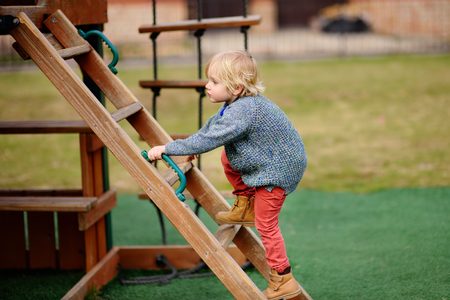 Photo for Cute little boy having fun on outdoor playground. Spring/summer/autumn active sport leisure for kids. Outdoors wooden equipment for children game - Royalty Free Image