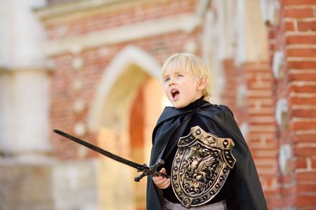 Photo for Portrait of a cute little boy dressed as a medieval knight with a sword and a shield. Medieval festival or costume party for kids - Royalty Free Image